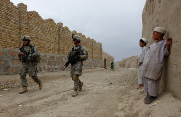 US Army soldiers walk through village during patrol in Kandahar region