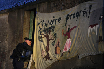 A French riot policeman inspects a house squatted by anti-airport protesters on the land that will become the new airport in Notre-Dame-des-Landes