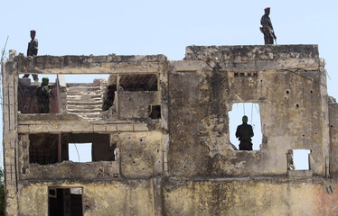 Members of Somalia's military forces stand guard at a ruined building during the arrival of Djibouti's President Guelleh at the Aden Abdulle International Airport in Somalia's capital Mogadishu