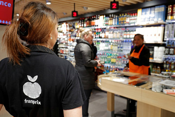 Customers wait to pay at a Franprix store in Paris