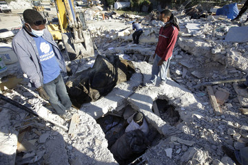 People search for victims in a destroyed building after an earthquake in Port-au-Prince