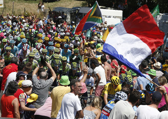 A supporter waves a French flag during the traditional Bastille Day, as the pack of riders climb during the 10th stage of the Tour de France cycling race