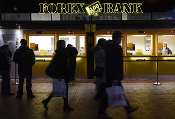 People pass a currency exchange office at the main station in Copenhagen