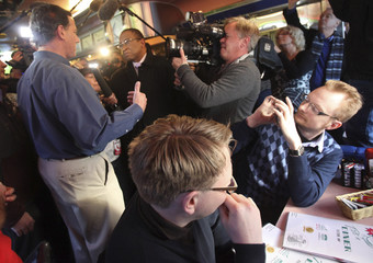 A man takes a photo of Republican presidential candidate and former Senator Rick Santorum during a campaign stop at the Tilt'n Diner in Tilton, New Hampshire