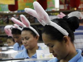 Cashiers wear rabbit ear headbands inside a supermarket in Chinatown