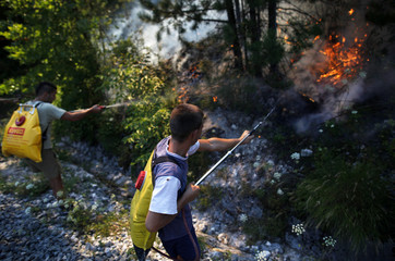 Firefighters and locals spray water on a forest fire in Donja Jablanica