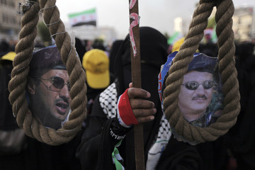 A woman carries a gallows rope during a protest outside the home of Yemeni President Abd-Rabbu Mansour Hadi, to demand the dismissal of the rest of the family members of former President Saleh, in Sanaa