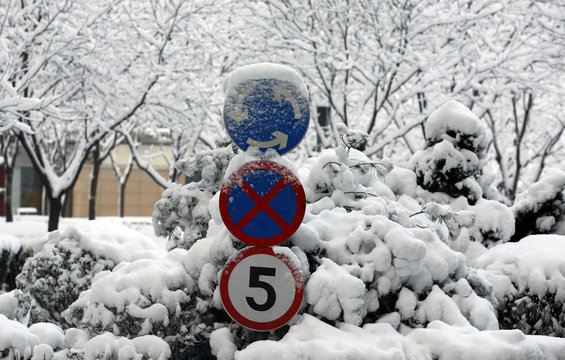 Traffic signs are covered with snow at a residential complex in Beijing