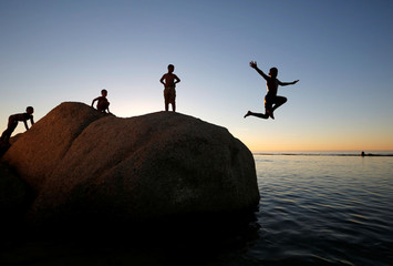 Children leap into a tidal pool as temperatures soar at Camps Bay beach in Cape Town