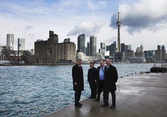 Canada's PM Harper, Minister of Finance Flaherty, Mayor of Toronto Ford, chair of the board of the Toronto Port Authority Mark McQueen pose front of the skyline at Billy Bishop Toronto City Airport in Toronto