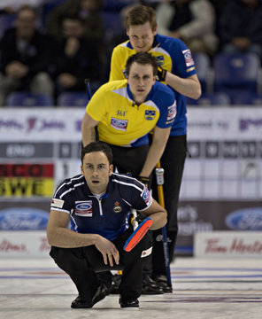 Scotland skip Murdoch watches the line of a shot as Sweden's Kjall and Lindberg watch from behind during their page playoff game at the World Men's Curling Championships in Victoria