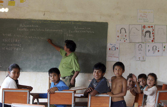 Native Paraguayan children from the Guarani tribe react to the camera while their math teacher writes on a blackboard at a school in Canindeyu