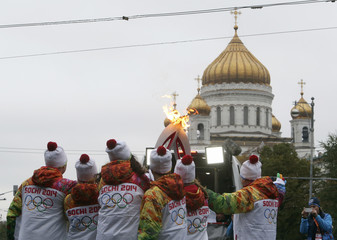 Participants take part in the Sochi 2014 Winter Olympic torch relay, with the Christ the Saviour Cathedral seen in the background, in central Moscow