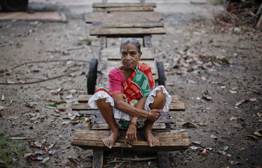 Gayatri, 70, sits on a handcart, which her family rents out to labourers, outside her house in Mumbai