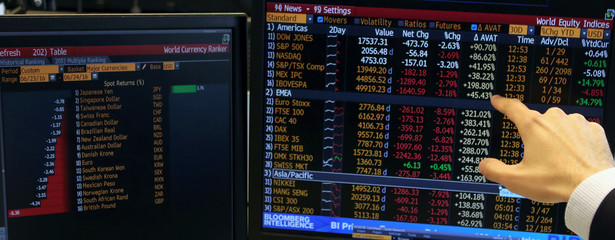 A trader from Guide brokerage company points at screens with the world equity indices and world currency rankers, in Sao Paulo