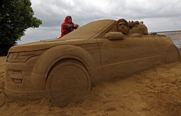 Artist creates a sand sculpture on a beach of the Peter and Paul Fortress in St. Petersburg