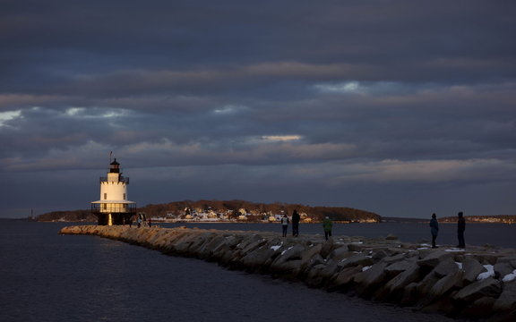 People make their way along a breakwater leading to Spring Point Ledge Lighthouse, completed in 1897, as the sun sets on New Year's Day, in South Portland, Maine