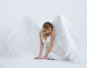 beautiful young model with big angel wings sitting in the studio. white background.