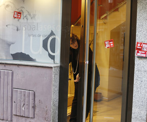 A woman fixes the door of a shop after it was damaged by protesters during a strike in Madrid