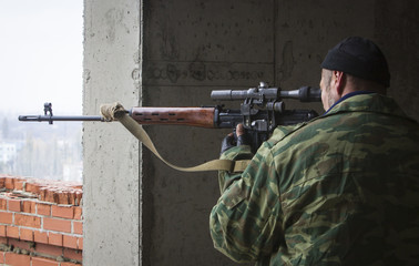 A pro-Russian rebel looks through the scope of his sniper rifle on an area near the airport in Donetsk, eastern Ukraine