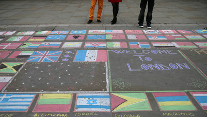 People look at a chalk mural drawn in remembrance of the victims of the Paris attacks, outside the National Gallery in central London