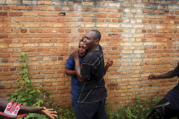 A man tries to protect a female police officer accused of shooting a protestor from other protesters in the Buterere neighbourhood of Bujumbura