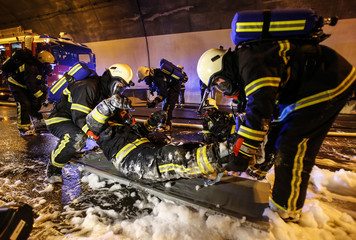 Firefighters take care of colleague playing part of an injured person during an exercise in the Loibl Tunnel in the southern Austrian village of Ferlach