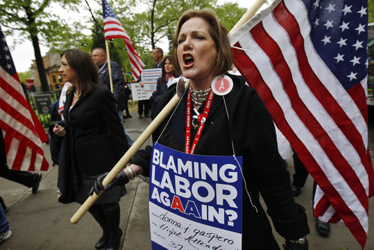 An American Airlines flight attendant marches with a U.S. flag during a rally to save jobs at American Airlines and American Eagle in New York