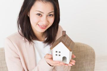 家のミニチュアを持つ女性