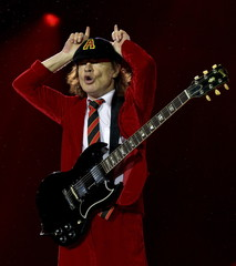 Veteran rock band AC/DC's lead guitarist Young makes a devil horns symbol with his hands as they perform their first concert in Australia on their 'Rock or Bust' world tour in Sydney