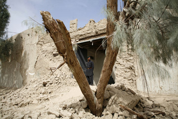 A survivor of an earthquake stands on rubble of a mud house after it collapsed following the quake in the town of Mashkeel