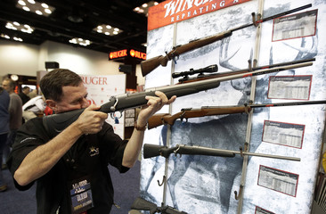 Mark Waters, of Cincinnati, looks over a rifle at the National Rifle Association's annual convention in Indianapolis