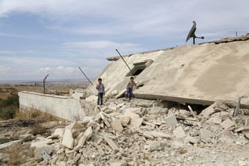 Children walk on rubble of a damaged building in the town of Marshamsha, in the southern province of Idlib