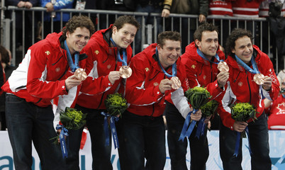 Switzerland's curling team celebrate with their bronze medals at the Vancouver 2010 Winter Olympics