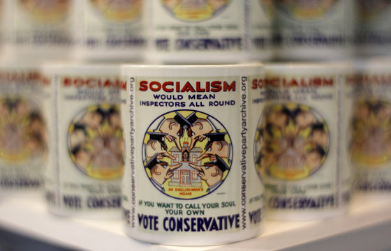 Mugs embossed with reproductions of vintage political posters stand on shelves on an exhibition stall on the first day of the Conservative Party's annual conference in Manchester