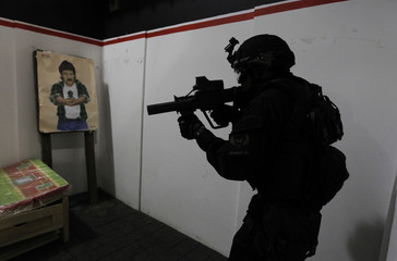 A Colombian police officer prepares to rescue a mock kidnap victim during a training simulation, at a photo opportunity in Sibate