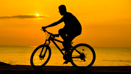 silhouette of man cycling on sunset