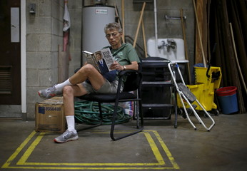 An attendee at a campaign stop for U.S. Republican presidential candidate Senator Rand Paul of Kentucky reads his book as she waits for his arrival at Royal Kitchen and Bathroom Cabinets in Niles, Illinois