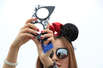 A girl takes pictures after opening ceremony at Shanghai Disney Resort in Shanghai