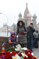 People come to lay flowers at the site where Boris Nemtsov was shot dead, with St. Basil's Cathedral seen in the background, in central Moscow