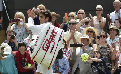Roger Federer of Switzerland walks off the court after defeatingTommy Robredo of Spain in their men's singles tennis match at the Wimbledon Tennis Championships, in London