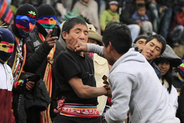 """An Andean man receives a punch during a one-on-one fight during the """"Takanakuy"""", a traditional festivity in Cuzco"""
