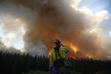 A firefighter watches a burnout operation on the north flank of the Fontenelle Fire outside Big Piney, Wyoming