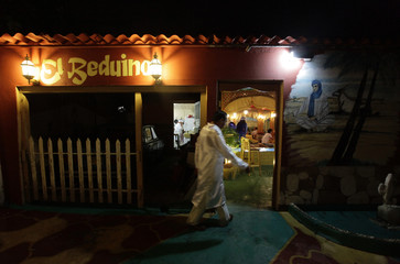 """A waiter walks in front of the entrance of a newly opened, privately-licensed Middle Eastern restaurant """"El Beduino"""" in Havana"""