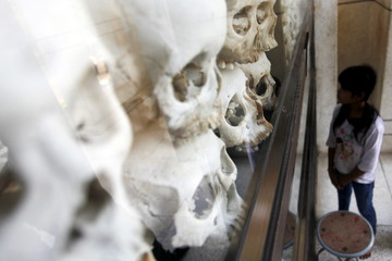 """Girl looks at the skulls and bones of more than 8,000 victims of the Khmer Rouge regime in a glass case at Choeung Ek, a """"Killing Fields"""" site located on the outskirts of Phnom Penh"""