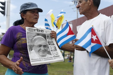 A woman holds a newspaper with a picture of Pope Francis as she speaks with a man holding Cuban and Vatican flags while they wait for his arrival outside the airport in Havana