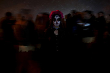 "A woman with her face painted as the popular Mexican figure ""Catrina"" poses for a photograph during Day of the Dead celebrations in Ciudad Juarez"