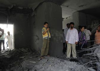 Boy takes pictures of the damage at the house of Saif Al-Arab Gaddafi, son of Libyan leader Muammar Gaddafi, in Tripoli