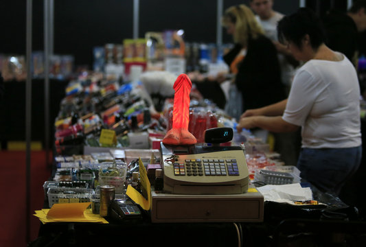 """An illuminated dildo sits on top of a cash register at a sex toy booth during the opening day of the 16th """"Venus"""" erotic fair in Berlin"""