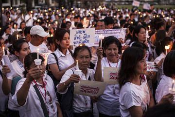People hold candles as they take part in an anti-violence campaign in central Bangkok